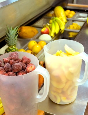 Strawberry, Pineapples, Peaches, and fresh fruits on stainless steel juice bar